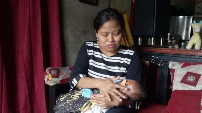 Lisdawati (40) ibunda AP sedang merawat bayi perempuannya setelah diperbolehkan pulang dari rumah sakit oleh dokter, Sabtu (23/11/2019)