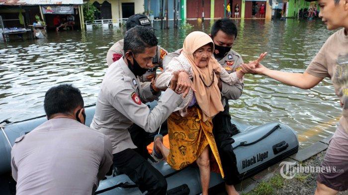 Petugas kepolisian dari SAR Polda Jateng sedang mengevakuasi lansia dari dalam Kampung Kaligawe, Kelurahan Tambakrejo, Kecamatan Gayamsari, Kota Semarang, Jawa Tengah, yang terdampak banjir, Minggu (7/2/2021). Dari pantauan Tribun Jateng, ketinggian air mencapai lutut orang dewasa, sedangkan di perkampungan mencapai perut orang dewasa. Sejumlah warga lanjut usia dievakuasi menggunakan perahu karet milik petugas SAR Polda Jawa Tengah ke lokasi yang lebih aman. Selain itu, kondisi banjir itu juga dimanfaatkan warga sekitar untuk menjaring ikan di tengah air yang menggenang. Akses jalan lumpuh total sehingga transportasi umum tidak tampak beroperasi. Hanya terlihat beberapa jenis kendaraan berat pengangkut barang yang menerjang banjir. Tribun Jateng/Hermawan Handaka