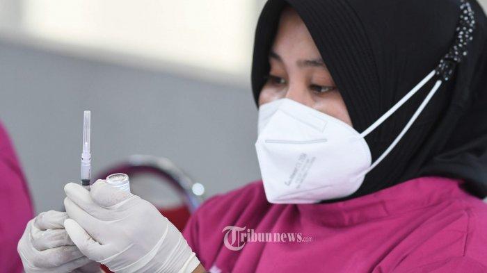 VAKSINASI WARGA PESISIR - Vaksinator menyiapkan vaksin yang akan diberikan kepada sekitar 1.500 warga pesisir di Surabaya dalam serbuan vaksin covid-19 gratis yang digelar TNI AL, Selasa (6/7/2021). Vaksinasi untuk masyarakat maritim Surabaya kali ini dipusatkan di Gedung Balai Prajurit Kalianak, Surabaya yang digelar Lantamal V Surabaya bersama Akademi Angkatan Laut (AAL). SURYA/AHMAD ZAIMUL HAQ