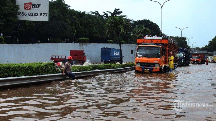 Sejumlah kendaraan terjebak banjir di ruas jalan Tol JORR TB Simatupang, Jakarta Selatan, Sabtu (20/2/2021). Banjir yang disebabkan tingginya curah hujan tersebut mengakibatkan kemacetan panjang di jalan Tol JORR TB Simatupang, namun kendaraan masih bisa melaju dengan kecepatan 20 hingga 30 kilometer/jam. Tribunnews/Jeprima