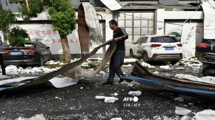 Seorang pria membersihkan kerusakan setelah tornado menghantam kota Suzhou di provinsi Jiangsu timur China pada 15 Mei 2021.