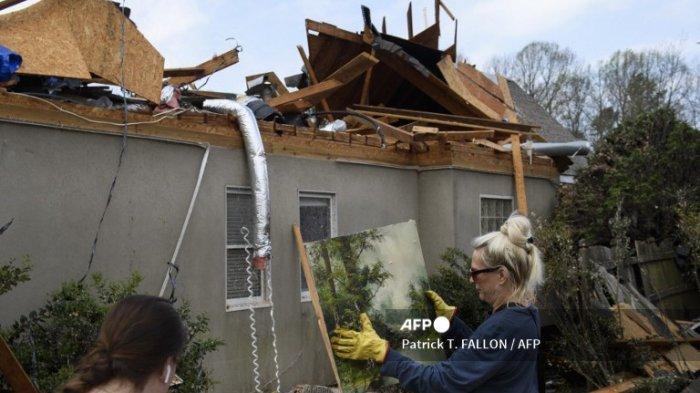 Seorang sukarelawan mengambil lukisan yang ditemukan di puing-puing di sekitar rumah yang hancur pada 26 Maret 2021, menyusul tornado yang melanda komunitas Eagle Point di selatan Birmingham, Alabama.