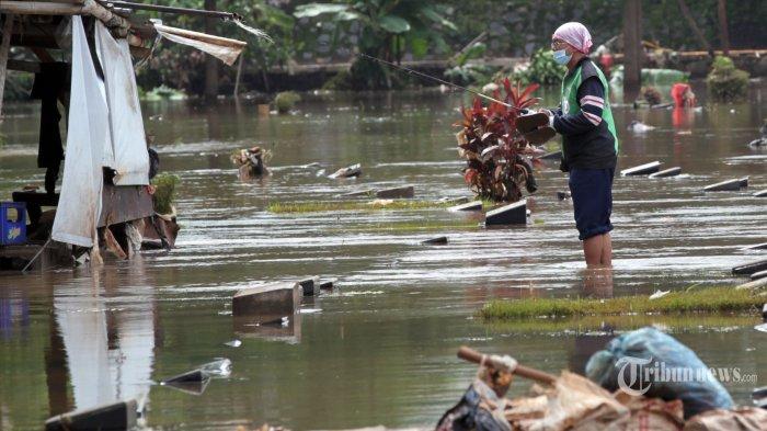 Warga memancing di tengah makam yang terendam banjir di TPU Jeruk Purut, Jakarta Selatan, Sabtu (20/2/2021). Hujan dengan intensitas tinggi pada Sabtu dini hari membuat kawasan pemakaman tersebut terendam banjir. Hingga pukul 14.30 WIB banjir setinggi 50 sentimeter masih menutupi sebagian makam. Tribunnews/Jeprima