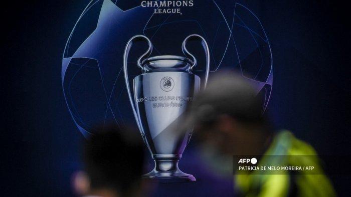 Orang-orang berdiri di depan papan reklame yang menggambarkan trofi Liga Champions UEFA di Porto pada 28 Mei 2021 pada malam pertandingan final Liga Champions UEFA antara Manchester City dan Chelsea di stadion Dragao.