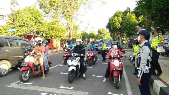Garis batas berhenti kendaraan roda dua di simpang Kembang Ijo Tuban Jawa Timur dibuat agar pengendara roda dua tetap menjaga jarak aman atau physical distancing.