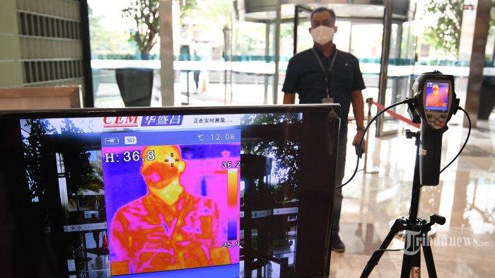 Pengunjung diperiksa suhu tubuh dengan thermal scanner sebelum memasuki Tunjungan Plaza, Kota Surabaya, Jawa Timur, Jumat (29/5/2020). Selain menerapkan aturan one way system untuk menghindari pengunjung saling berpapasan satu sama lain, Tunjungan Plaza juga membatasi banyaknya pengunjung di gerai sesuai luas gerai dan pembatasan keluar masuk pengunjung di setiap gerai. Hal tersebut dilakukan jelang pemberlakuan new normal di Kota Surabaya. Surya/Ahmad Zaimul Haq
