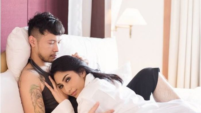 Tyas Mirasih dan suami berfoto di ranjang.