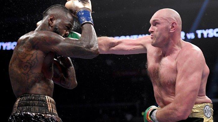 Tyson Fury (kanan) memukul Deontay Wilder (kiri)