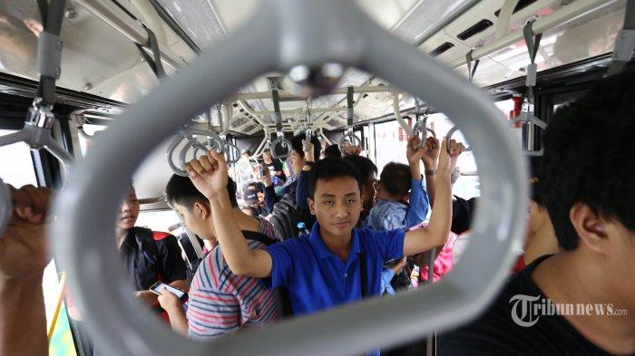 Warga naik Bus Transjakarta.
