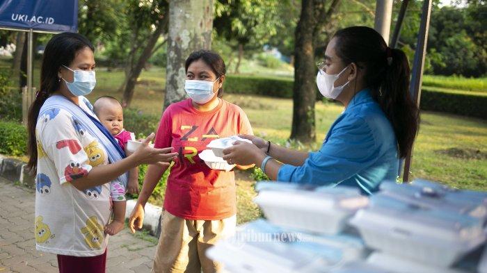 Sejumlah mahasiswa civitas akademi Universitas Kristen Indonesia memberikan  makanan gratis kepada masyarakat di area kampus UKI Cawang, Jakarta, Selasa (16/3/2021). Kegiatan UKI Peduli dan Berbagi ini digelar selama 3 bulan dengan memberikan 500 bungkus nasi, masker dan vitamin dalam meringankan beban masyarakat di tengah situasi Pandemi Covid 19. TRIBUNNEWS/IRWAN RISMAWAN