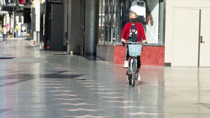 Berikut update terbaru pasien virus corona di seluruh dunia hingga Senin 27 April 2020, FOTO: Sejumlah negara di dunia mulai melakukan buka tutup kebijakan pembatasan sosial COVID-19. Langkah uji coba ini dilakukan untuk memperbaiki perekonomian negara. Foto: Seorang perempuan mengenakan masker dan mengendarai sepeda di Hollywood Blvd yang sepi di tengah pandemi virus corona pada 15 April 2020 di Los Angeles, California.