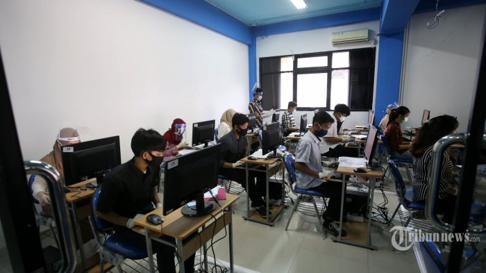 Sejumlah peserta tengah mengikuti Ujian Tulis Berbasis Komputer (UTBK) Seleksi Bersama Masuk Perguruan Tinggi Negeri (SBMPTN) yang dilaksanakan di Universitas Negeri Jakarta (UNJ), Jakarta Timur, Minggu (5/7/2020). Rangkaian UTBK SBMPTN 2020 gelombang pertama mulai dilaksanakan oleh sejumlah perguruan tinggi negeri di Indonesia hari ini. Panitia dan peserta menerapkan protokol kesehatan Covid-19 secara ketat, yakni antara lain pengukuran suhu tubuh, penggunaan masker dan sarung tangan, serta jaga jarak aman (physical distancing). Warta Kota/Angga Bhagya Nugraha