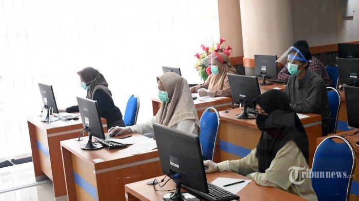 Peserta mengikuti Ujian Tulis Berbasis Komputer (UTBK) di Universitas Airlangga (Unair), Kota Surabaya, Jawa Timur, Minggu (5/7/2020). UTBK yang diikuti 31.242 peserta itu selain memberlakukan protokol kesehatan juga mewajibkan peserta menunjukkan surat keterangan hasil rapid test guna mencegah penyebaran virus corona (Covid-19). Surya/Ahmad Zaimul Haq