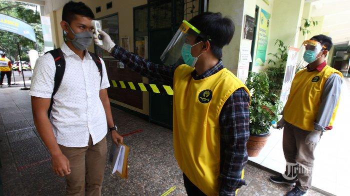 Panitia dan peserta menerapkan protokol kesehatan Covid-19 secara ketat dalam pelaksanaan Ujian Tulis Berbasis Komputer (UTBK) Seleksi Bersama Masuk Perguruan Tinggi Negeri (SBMPTN) Intitut Teknologi Bandung (ITB) 2020, di SMAN 5, Jalan Belitung, Kota Bandung, Jawa Barat, Minggu (5/7/2020). Ujian masuk perguruan tinggi negeri ITB di saat pandemi Covid-19 ini, setiap peserta wajib mengenakan masker medis, masuk ke tempat ujian diperiksa suhu tubuh dan membersihkan tangan dengan hand sanitizer, masuk ke ruang ujian jaga jarak aman (physical distancing) dan harus membersihkan tangan dengan hand sanitizer, serta jarak tempat duduk peserta di ruang ujian diatur lebih renggang. Sementara setiap panitia mengenakan masker medis, face shield (pelindung wajah), dan sarung tangan. Pelaksanaan UTBK SBMPTN ITB gelombang pertama pada 5-14 Juli 2020 dan dilanjut gelombang kedua pada 20-29 Juli 2020. Tribun Jabar/Gani Kurniawan