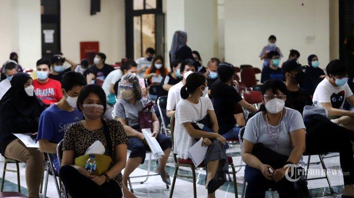 Sejumlah warga mengantre untuk menerima vaksin Covid-19 Pfizer di Gedung Judo, Kelapa Gading, Jakarta Utara, Senin (23/8/2021). Program vaksinasi Covid-19 memakai vaksin Pfizer saat ini baru bisa digunakan untuk masyarakat berusia 18 tahun ke atas. Hingga Minggu (22/8), vaksinasi dosis pertama di Jakarta telah mencapai 9,3 juta orang. Sementara untuk dosis kedua baru mencapai 4,8 juta. Pemprov DKI telah meningkatkan target vaksinasi dari 8,8 juta menjadi 11 juta orang. Tribunnews/Jeprima