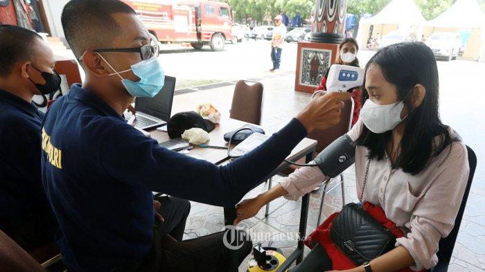 Tenaga kesehatan Pusdokkes Polda Papua saat memeriksa kesehatan penerima vaksin di ajang  Pekan Olahraga Nasional (PON) XX di Gedung Auditorium Universitas Cendrawasih, Jayapura, Papua, Jumat (8/10/2021).