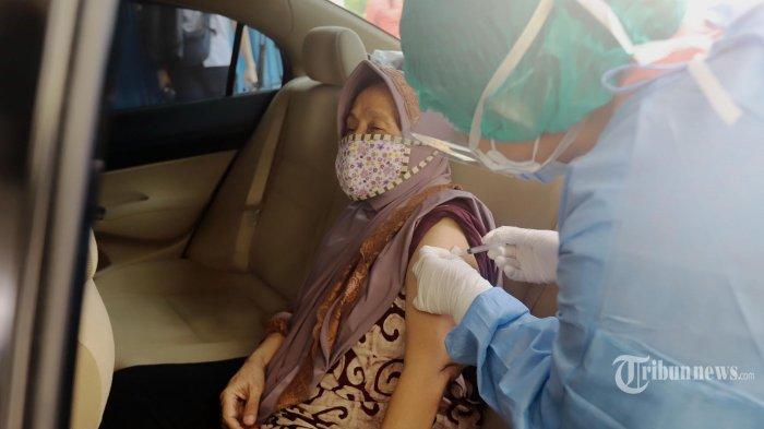 Petugas kesehatan melakukan vaksinasi Covid-19 kepada warga lansia secara drive thru di Kemayoran Jakarta, Rabu (3/3/2021). Kementerian Kesehatan menggandeng penyedia jasa layanan kesehatan daring yaitu Halodoc menyediakan layanan vaksinasi secara drive thru bagi warga yang masuk dalam kategori lanjut usia (lansia) agar protokol kesehatan dapat diterapkan dengan mengurangi kerumunan karena para lansia tidak perlu mengantre hingga panjang. TRIBUNNEWS/HERUDIN