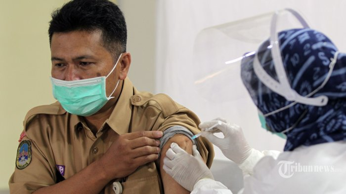 Petugas menyuntikkan vaksin Covid-19 kepada tenaga pengajar dalam acara vaksinasi massal di SMA Negeri 70 Bulungan, Kebayoran Baru, Jakarta Selatan, Rabu (24/2/2021). Sebanyak 600 orang guru, dosen, dan tenaga pendidikan mengikuti acara tersebut. Pemerintah memulai tahap vaksinasi Covid-19 untuk guru, tenaga pendidikan, dan dosen dengan target sebanyak 5.057.582 orang se-Indonesia. Tribunnews/Jeprima