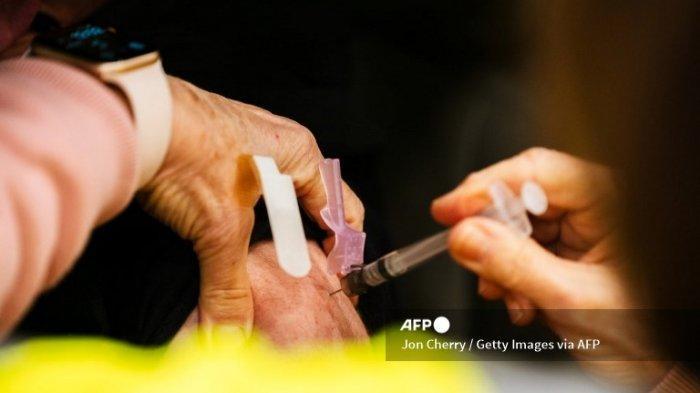 LOUISVILLE, KY - 04 JANUARI: Seorang petugas kesehatan memberikan vaksin kepada pasien di dalam kendaraan mereka selama hari pertama vaksinasi Moderna COVID-19 massal di Broadbent Arena di Kentucky State Fair and Exposition Center pada 4 Januari 2021 di Louisville, Kentucky . Senin menandai hari pertama vaksinasi drive-in massal di negara bagian itu. Petugas kesehatan adalah fokus utama vaksinasi, seperti yang diamanatkan oleh pemerintah federal.