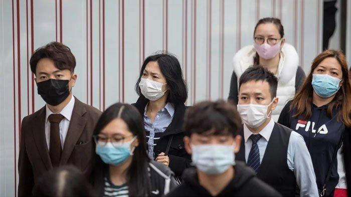 Orang-orang yang memakai masker pelindung saat berjalan di distrik Kwun Tong Hong Kong pada 23 Januari.