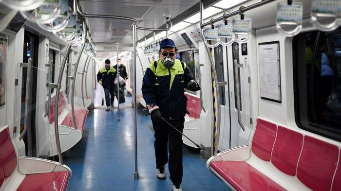 Petugas menyemprotkan disinfektan pada kereta bawah tanah China di hari pertama kerja di Beijing, China, Senin (10/2/2020).