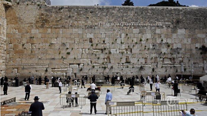Orang-orang Yahudi Ultra-Ortodoks menghadiri doa khusus untuk mengakhiri pandemi COVID-19 sambil menjaga jarak dua meter dari satu sama lain di Tembok Barat, situs paling suci Yudaisme, di Yerusalem. Rabu (25/3/2020). Israel mengikuti pembatasan ketat untuk menahan penyebaran coronavirus. (AFP/MENAHEM KAHANA)