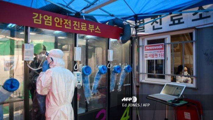 Seorang pria berbicara kepada seorang perawat selama tes virus corona di sebuah bilik pengujian di luar RS Yangji, Seoul, Selasa (17/3/2020). Sebuah rumah sakit di Korea Selatan telah memperkenalkan