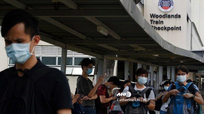 Orang-orang, yang memakai masker sebagai tindakan pencegahan terhadap coronavirus novel COVID-19, tiba di pos pemeriksaan Woodlands di Singapura pada 17 Maret 2020, dari seberang jalan lintas negara bagian selatan Malaysia, Johor.