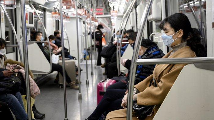 Penumpang kereta bawah tanah di Beijing mengenakan masker pada hari pertama kerja, Senin (10/2/2020).