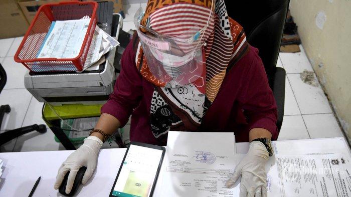 Untuk mencegah penyebaran virus corona (Covid-19), warga yang mengurus surat-surat di Kecamatan Tambaksari, Kota Surabaya, Jawa Timur, diharuskan mengenakan face shield (pelindung wajah), Selasa (23/6/2020). Selain kewajiban mengenakan face shield baik bagi warga yang mengurus maupun petugas, protokol kesehatan lainnya juga diterapkan yakni kewajiban cuci tangan sebelum masuk, pengecekan suhu tubuh, dan pembatasan jarak di ruangan serta maksimal hanya enam warga yang ada di ruangan layanan. Surya/Ahmad Zaimul Haq