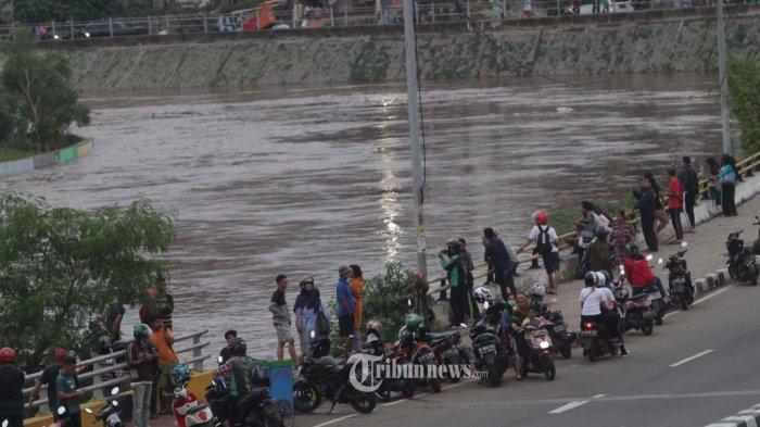 NONTON AIR----Warga asyik menonton tinggi  aliran  air  yang mengalir di Kali Ciliwung  dari Jalan Abdulah Syafei, Bukit Duri, Jakarta Selatan Rabu(1/1/2020).--Warta Kota/henry lopulalan