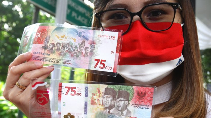 Warga memperlihatkan uang kertas baru pecahan Rp 75.000 usai proses penukaran penukaran di halaman Kantor Perwakilan wilayah (KPw) Bank Indonesia (BI) Provinsi Jawa Barat, Jalan Perintis Kemerdekaan, Kota Bandung, Selasa (18/8/2020). Uang baru Rp 75.000 merupakan edisi spesial HUT ke-75 Kemerdekaan Republik Indonesia yang dicetak terbatas hanya sebanyak 75 juta lembar, sementara KPw BI Jabar akan mendistribusikan 7,6 juta lembar. Cara penukarannya melalui preorder ke portal BI, https//pintar.bi.go.id untuk mendapatkan jadwal penukaran, setiap satu No. KTP hanya dapat menukarkan 1 lembar uang Rp 75.000. Periode penukaran akan belangsung hingga 30 September 2020. (TRIBUN JABAR/GANI KURNIAWAN) (TRIBUN JABAR/TRIBUN JABAR/GANI KURNIAWAN)