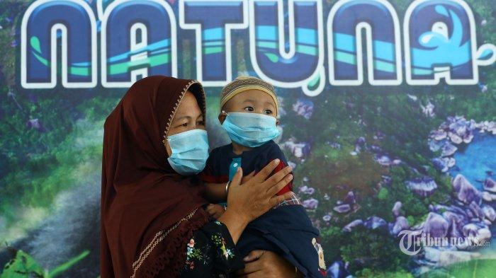 Warga menggunakan masker saat tiba di Bandara Raden Sadjad, Natuna, Kepulauan Riau, Senin (3/2/2020). Pasca Pulau Natuna dijadikan tempat observasi WNI yang dievakuasi dari Wuhan, warga sekitar melakukan aktivitas menggunakan masker. TRIBUNNEWS/IRWAN RISMAWAN