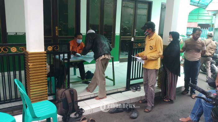BST TAHAP II - Warga Rt 06/04 Kelurahan Duri Selatan, Tambora, Jakarta Barat, antri dengan tertib saat mencairkan dana bantuan sosial tunai (BST), Kamis (18/2/2021). Bantuan ini disalurkan langsung oleh petugas PT Pos Indonesia, kepada 373 keluarga penerima manfaat di wilayah ini yang terdampak Covid-19, sebesar Rp 300 ribu. WARTA KOTA/NUR ICHSAN