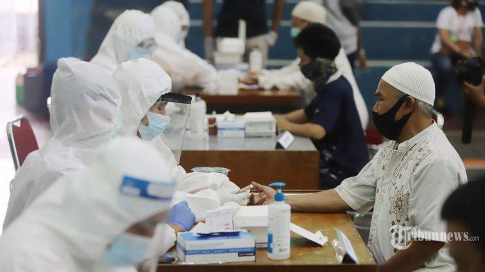 Tenaga medis melakukan rapid test (tes cepat) Covid-19 terhadap warga di Gelanggang Remaja Kecamatan Tebet, Jakarta Selatan, Senin (23/11/2020). Polda Metro Jaya menyelenggarakan bakti sosial penyemprotan cairan disinfektan dan rapid test atau tes cepat Covid-19 karena adanya temuan kasus terkonfirmasi positif Covid-19 dari jemaah Maulid Nabi Muhammad SAW yang diselenggarakan di kawasan Tebet.