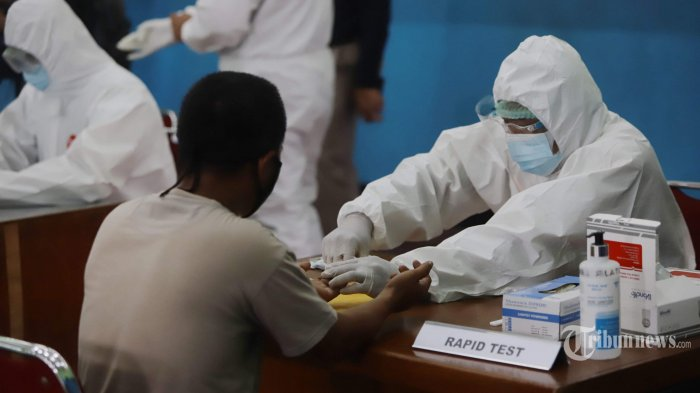 Tenaga medis melakukan rapid test (tes cepat) Covid-19 terhadap warga di Gelanggang Remaja Kecamatan Tebet, Jakarta Selatan, Senin (23/11/2020). Polda Metro Jaya menyelenggarakan bakti sosial penyemprotan cairan disinfektan dan rapid test atau tes cepat Covid-19 karena adanya temuan kasus terkonfirmasi positif Covid-19 dari jemaah Maulid Nabi Muhammad SAW yang diselenggarakan di kawasan Tebet. Tribunnews/Herudin