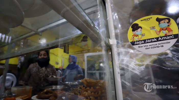 Seorang warga saat menikmati makan siang di Warung Tegal (Warteg) Ellya, Cilandak Timur, Pasar Minggu, Jakarta Selatan, Senin (20/7/2020). Menurut pemilik Warteg Ellya, sejak dimulainya penerapan PSBB transisi, unit usahanya telah melakukan penerapan protokol kesehatan pencegahan penyebaran COVID-19 seperti pembatasan jarak fisik, menyediakan area cuci tangan, mewajibkan pengunjung untuk menggunakan masker, serta penggunaan pelindung wajah dan sarung tangan untuk pelayan. Tribunnews/Jeprima