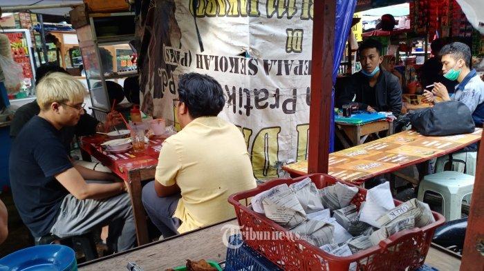 Warga sedang menikmati makanan yang dijual di kawasan perkantoran Jalan Sudirman, Jakarta Pusat,Jumat(8/1). Tampat yang menjual aneka makanan dan minuman ini  tidak memperhatikan protokol kesehatan yang di anjurkan oleh pemerintah untuk memutus mata rantai Covid 19. WARTA KOTA/HENRY LOPULALAN