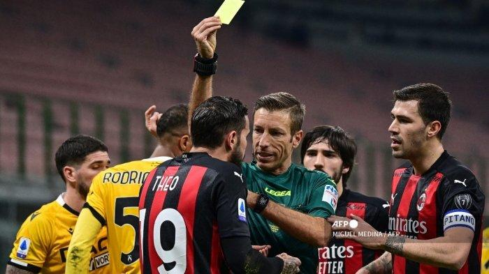 Wasit Italia Davide Massa (tengah) memberikan kartu kuning kepada bek Prancis AC Milan Theo Hernandez (Depan L) saat pertandingan sepak bola Serie A Italia AC Milan vs Udinese pada 03 Maret 2021 di stadion San Siro di Milan. MIGUEL MEDINA / AFP