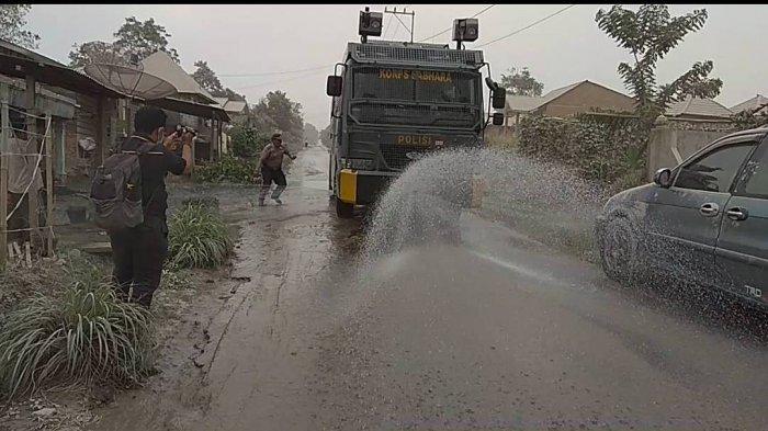 Polisi Keliling Desa-desa Siram Jalan yang Ditutupi Debu Sinabung
