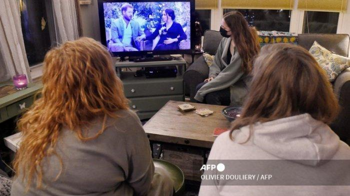 Ilustrasi foto ini menunjukkan orang-orang yang memakai masker wajah, menonton percakapan televisi antara <a href='https://kupang.tribunnews.com/tag/pangeran-harry' title='PangeranHarry'>PangeranHarry</a> dari Inggris dengan istrinya <a href='https://kupang.tribunnews.com/tag/meghan-markle' title='MeghanMarkle'>MeghanMarkle</a> dan pembawa acara AS <a href='https://kupang.tribunnews.com/tag/oprah-winfrey' title='OprahWinfrey'>OprahWinfrey</a>, di Arlington, Virginia 7 Maret 2021.