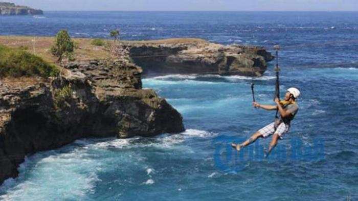 Seorang wisatawan mencoba wahana permainan flying fox di Dusun Ceningan, Klungkung, Bali beberapa waktu lalu.
