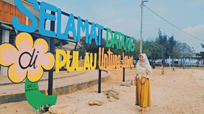 Wisatawan berpose dengan latar tulisan di Selamat Datang Pulau Untung Jawa