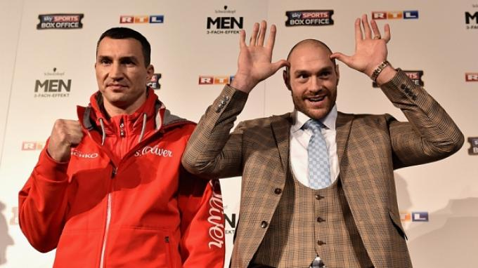 Wladimir Klitschko (kiri) tampak serius dalam sesi foto konferensi pers di Dusseldorf, Jerman, Kamis (26/11/2015) waktu setempat, sementara Tyson Fury meledek.