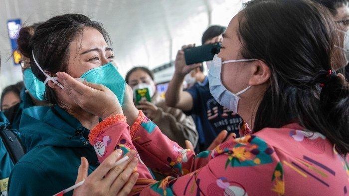 Seorang anggota staf medis (kiri) dari Rumah Sakit Medical College Peking Union menangis sebelum pergi di bandara Tianhe di Wuhan di provinsi Hubei tengah Cina pada 15 April 2020. Staf medis dari Rumah Sakit Medical College Peking Union adalah tim bantuan medis terakhir dari provinsi lain meninggalkan Wuhan setelah membantu upaya penanganan Virus Corona atau Covid-19.