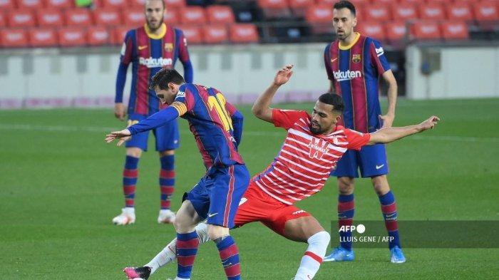 Gelandang Granada Venezuela Yangel Herrera (kanan) menantang penyerang Argentina Barcelona Lionel Messi selama pertandingan sepak bola Liga Spanyol antara Barcelona dan Granada di stadion Camp Nou di Barcelona pada 29 April 2021. LLUIS GENE / AFP