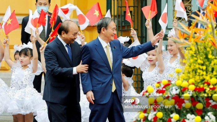 Perdana Menteri Jepang Yoshihide Suga (kanan) dan mitranya dari Vietnam Nguyen Xuan Phuc (kedua dari kiri) melambai kepada anak-anak dalam upacara penyambutan di Istana Kepresidenan di Hanoi pada 19 Oktober 2020.