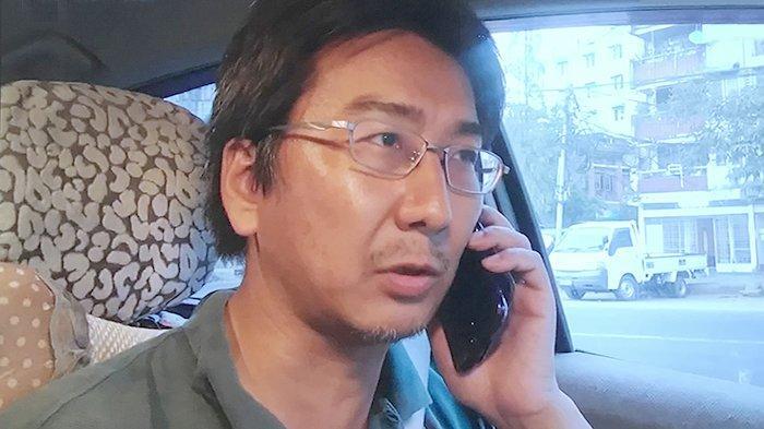 Yuki Kitazumi sedang menelepon di dalam mobilnya.