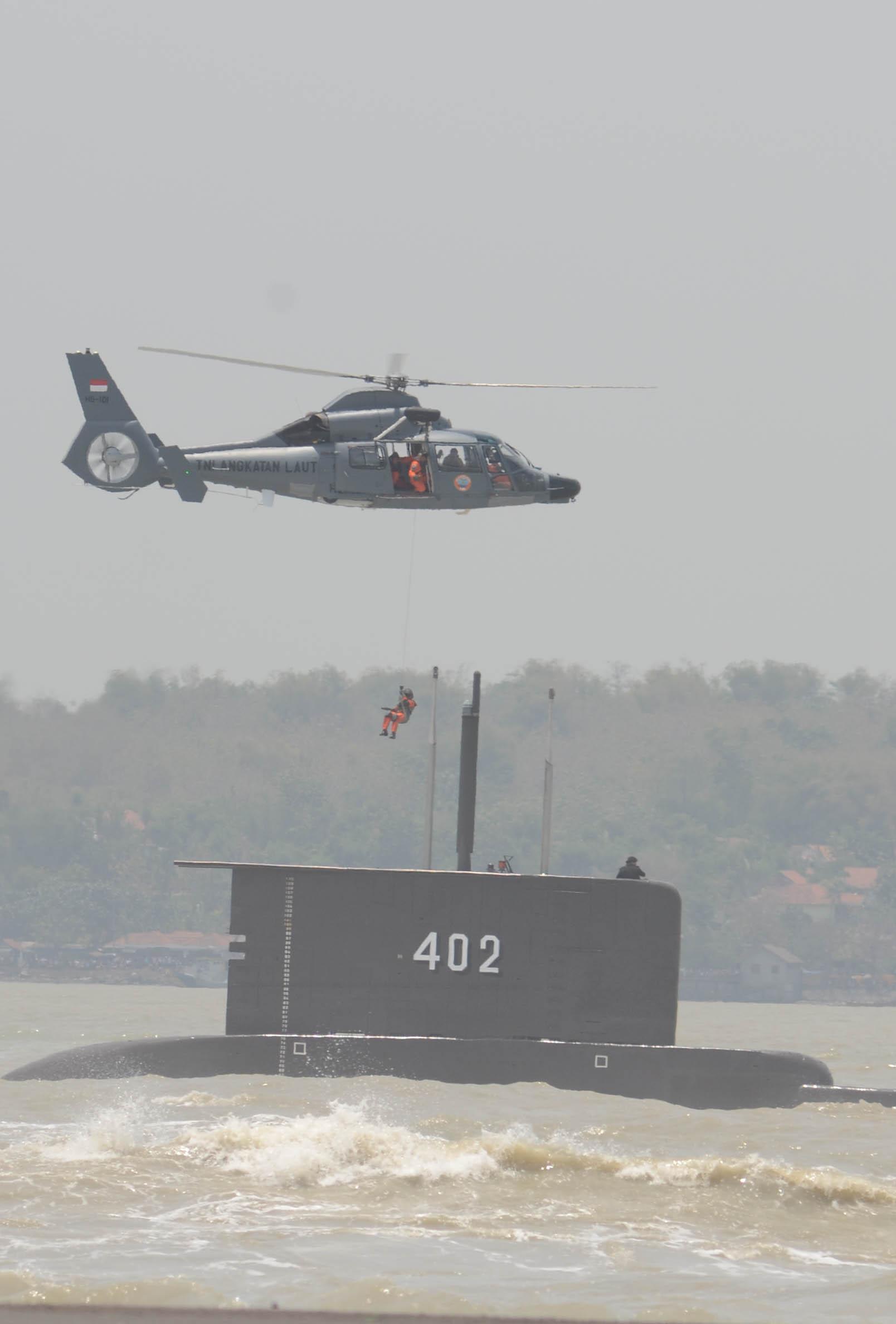Seorang anggota Tentara Nasional Indonesia (TNI) melakukan fast rope di atas kapal selam KRI Nanggala-402 untuk menyelamatkan korban saat perayaan HUT Ke-69 TNI di Dermaga Ujung, Koarmatim, Surabaya, Selasa (7/10/2014). Peringatan terbesar sepanjang sejarah TNI tersebut mengambil tema Patriot Sejati, Profesional, dan Dicintai Rakyat. SURYA/AHMAD ZAIMUL HAQ