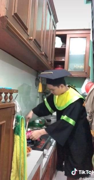 Mahasiswa wisuda online sambil masak nasi goreng.